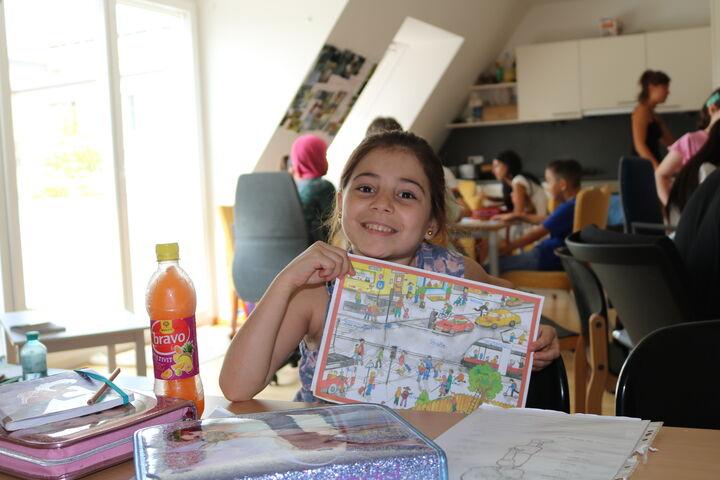 Stolz zeigt eine Schülerin, was sie heute bearbeitet hat (Bild: FSW)