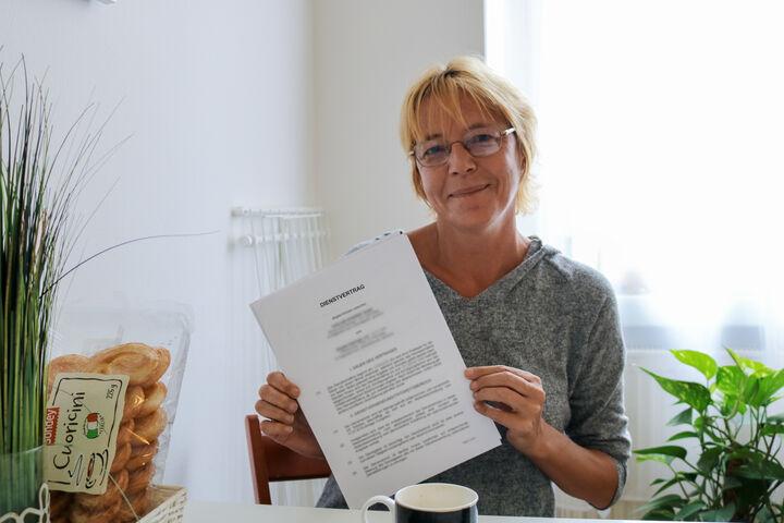 Frau H. zeigt stolz ihren Dienstvertrag. (Bild: FSW)
