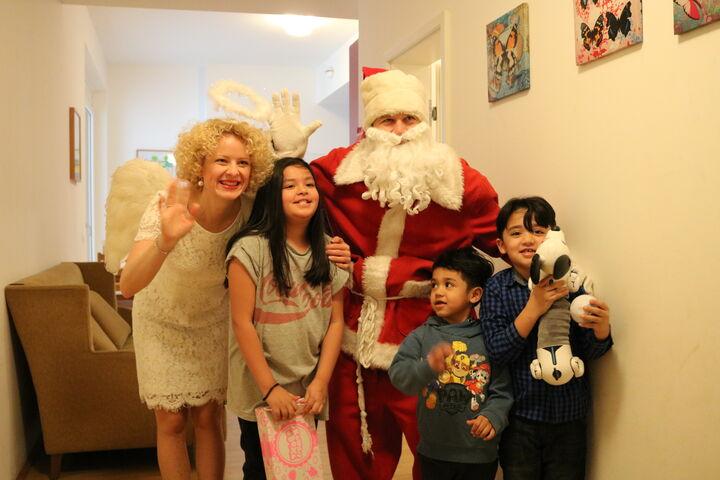 Zusammen mit Christkind, Weihnachtsmann und allen Geschenken posieren die zufriedenen Kinder. (Bild: FSW)