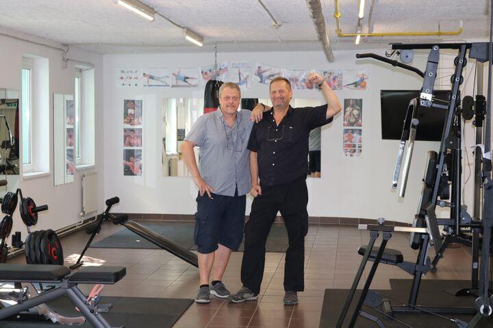 Peter und Gustl haben sichtlich Spaß bei der Hausführung und zeigen stolz Bizeps und Fitnessraum. (Bild: FSW)