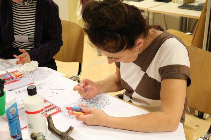 Eine Besucherin des Tageszentrums Obdach Ester konzentriert sich auf ihr Mandala. (Bild: FSW)