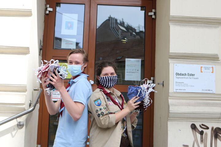 Pfadfinder Lukas und Pfadfinderin Saveria präsentieren die von ihrer Gruppe genähten und gespendeten Masken vor dem Tageszentrum Obdach Ester. (Bild: FSW)