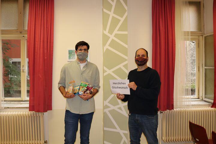 Teamleiter Markus Bousska gratuliert Güney und überreicht Studentenfutter zur Stärkung für neue Aufgaben. (Bild: FSW)