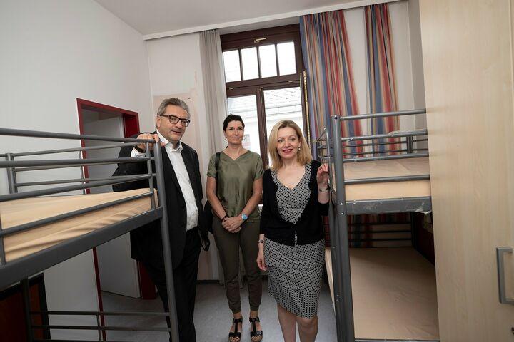 Stadtrat Peter Hacker, Geschäftsführerin von Obdach Wien, Doris Czamay und Geschäftsführerin des Fonds Soziales Wien, Anita Bauer sehen ein unbewohntes Zimmer im Obdach Favorita. (Bild: FSW)