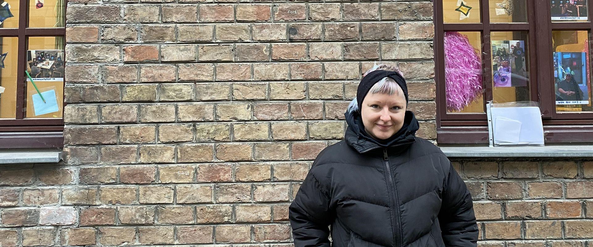 Sozialarbeiterin Julia Gleu vor den bebilderten Fenstern.