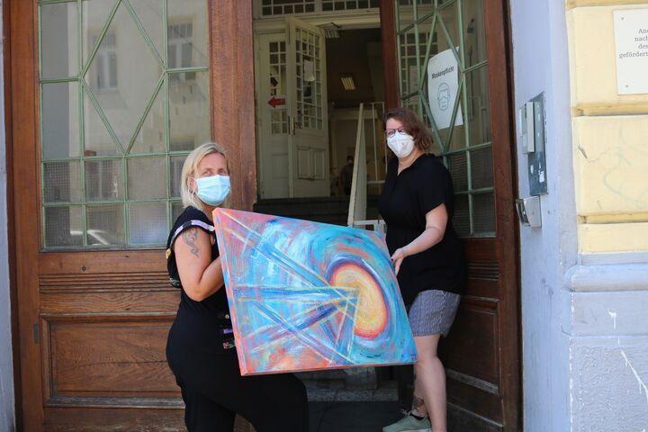 Spenderin Candy und Teamleiterin Kathrin tragen ein weiteres Gemälde ins Obdach Wurlitzergasse. (Bild: FSW)