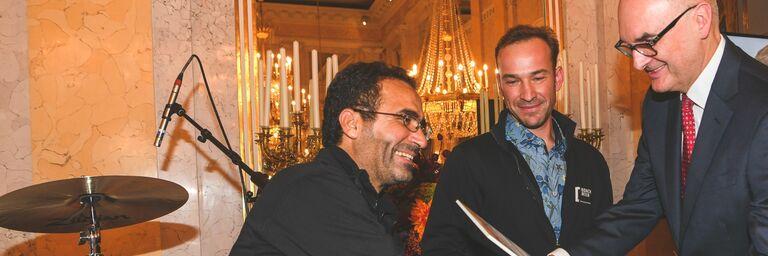 Monteur Watiq A. nimmt die Urkunde von Bank Austria-Vorstandsmitglied Jürgen Kullnigg entgegen (im Hintergrund Projektleiter Stefan Höfer). (Bild: Oreste Schaller )